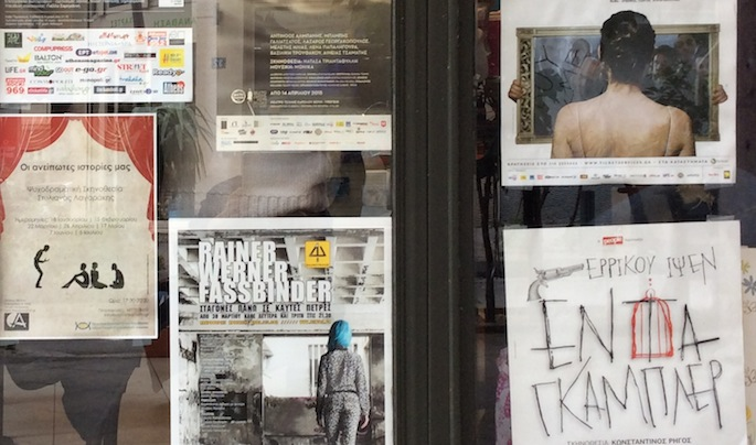 Theater posters in the window of an Athens café.
